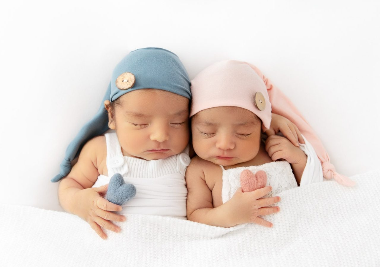 Newborn boy girl twins with arms around each other wearing blue and pink sleepy caps and holding blue and pink felted hearts
