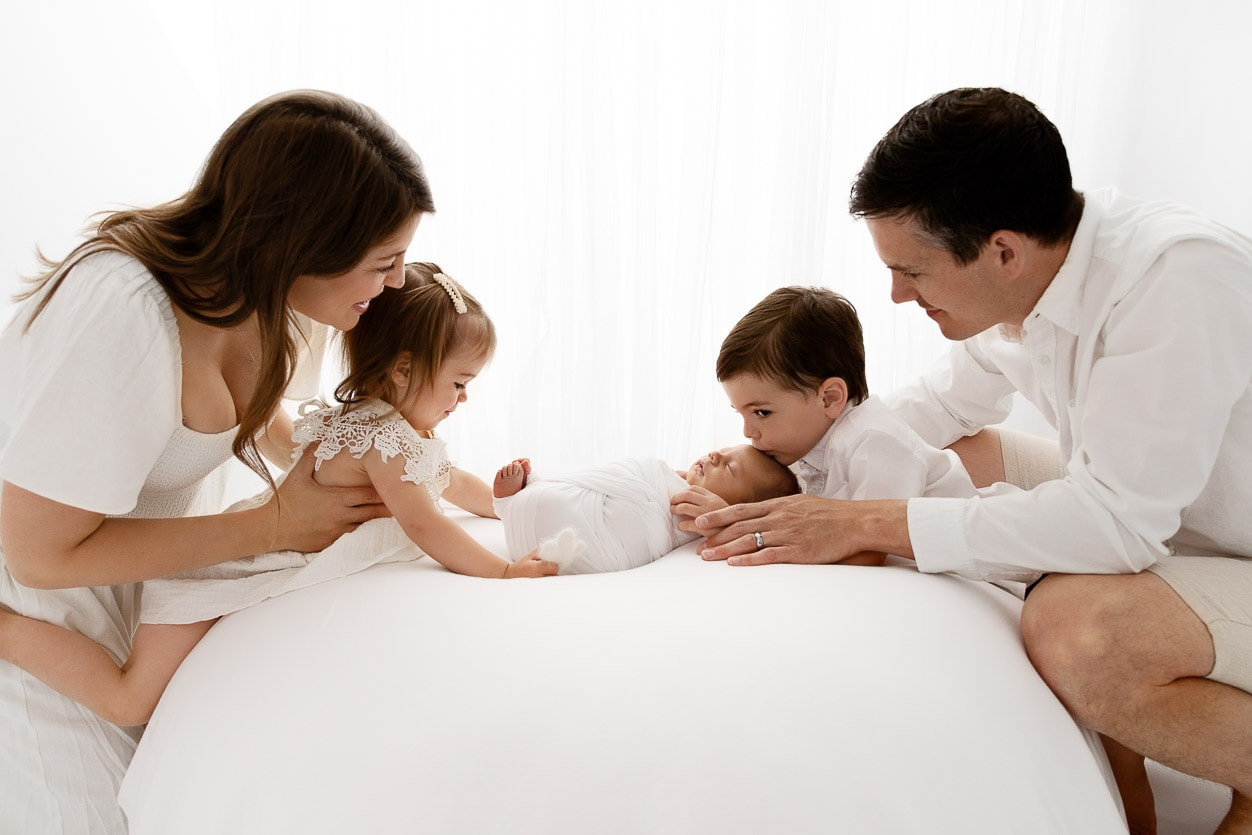Backlit family of 5 looking at their newborn baby boy in front of a bright white sheer curtain