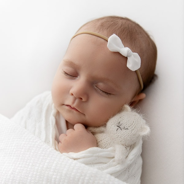 Newborn Baby girl swaddled in white sleeping while snuggling a white knit bear stuffie